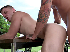 Fascinating gay dude getting screwed doggystyle by a tattooed stud outdoor