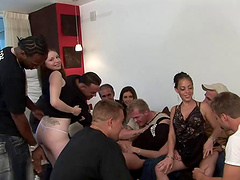 Sultry blonde sucks off a hung stud at a wild groupsex shoot