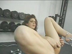 Doting blonde works on her cunt with a dildo at the gym