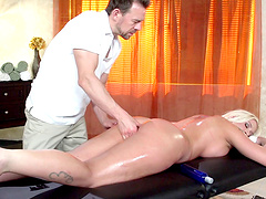 Tattooed blonde rides her masseur's cock after an oily massage