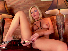 Charming blonde moans in pleasure as she plays with a huge dildo in a close shoot