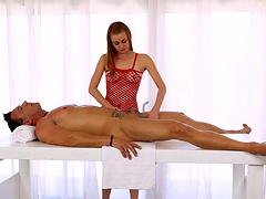 Leggy redhead masseuse milks a man's cock on the massage table