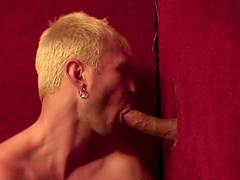 Handsome blonde guy sucks the large cock through a gloryhole