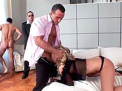 Busty blonde milf is on her knees pleasuring two wieners at once