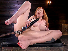 Submissive redhead Lauren Phillips mounts herself on a fuck machine