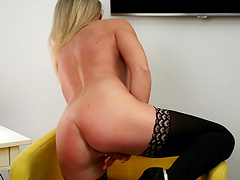 Horny MILF Queenie enjoys pleasuring her shaved pussy on the sofa