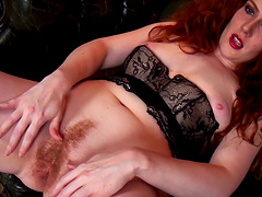 Stunning redhead Amy C fingers her hairy pussy on the chair