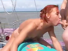 Redhead fucks two dudes on a yacht