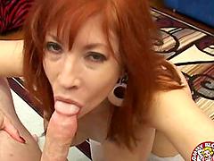 Redhead milf tramp with big tits sucks on a dick