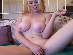 Busty blonde fingers her pink pussy after showing off her twins