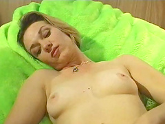 Naked slut fingers her snatch on a bed with huge-ass pillows