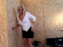 Busty blonde sucks on a big cock through a gloryhole