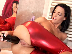Brunette whore sticks a huge dildo in her asshole
