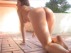 Video of a sexy amateur brunette playing naked in the back yard
